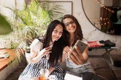 Zwei jugendliche lächelnde schöne dünne Mädchen mit dem langen dunklen Haar, tragende zufällige Kleidung, sitzen neben einander u lizenzfreies stockfoto