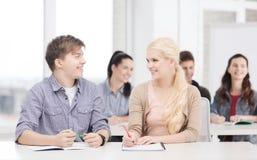 Zwei Jugendliche mit Notizbüchern in der Schule Lizenzfreies Stockfoto