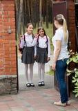 Zwei Jugendlichen, die Hände wellenartig bewegen, um bevor dem Gehen zur Schule zu bemuttern Stockbild