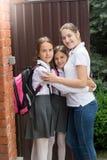 Zwei Jugendlichen, die mit Mutter bevor dem Gehen zur Schule umarmen Stockfotografie