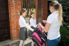 Zwei Jugendlichen, die zur Schule verlassen und Rucksäcke von der Mutter nehmen Stockfotografie