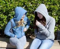 Zwei Jugendlichen, Sitzen und Unterhaltung Stockfotografie