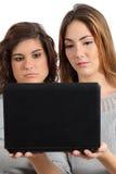 Zwei Jugendlichmädchen gebohrt, einen netbook Computer aufpassend Stockbilder