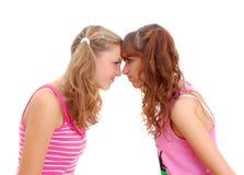 Zwei Jugendschwestern, die entlang einander anstarren Stockbild