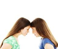 Zwei Jugendschwestern, die entlang einander anstarren Lizenzfreies Stockbild