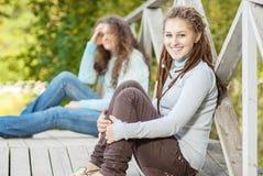 Zwei jung und schöne Mädchen an den Geländerdocken Stockbild