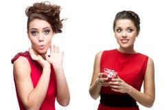 Zwei Junge überraschte Frauen im roten Kleid Lizenzfreies Stockfoto
