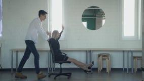 Zwei junge Arbeitnehmer, die auf Bürostuhl innerhalb des Produktionsbodens rollen stock video footage