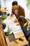 Zwei junge Architekten, die über Bauplänen während einer Sitzung schauen lizenzfreie stockfotografie