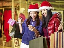 Zwei junge asiatische Frauen, die für Weihnachten kaufen stockbild