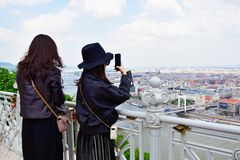 Zwei junge asiatische Frauen, die Fotos der szenischen Ansichten von Budapest machen lizenzfreie stockbilder