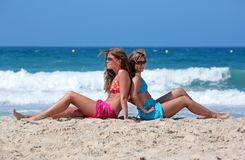 Zwei junge attraktive Frauen, die in der Sonne am Feiertag oder an VAC kühlen Stockfotos