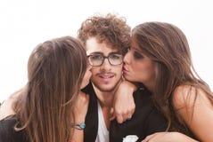 Zwei junge attraktive Frauen, die Mann küssen stockfotos