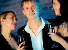 Zwei junge attraktive süße Frauen und Mann mit Champagnergläsern stockfotos