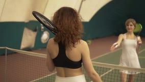 Zwei junge attraktive Tennisspieler rütteln Hände nahe dem Netz am Tennisplatz Sport und Erholung stock video