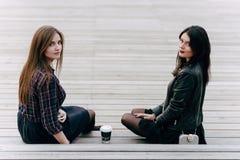 Zwei junge aufwerfende hübsche Frauen, beim Sitzen mit nehmen Kaffee auf hölzerne Treppe in der Frischluft weg, Lizenzfreie Stockbilder