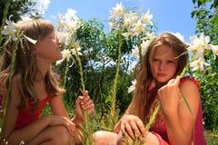 Zwei junge blonde Mädchen im Sommergarten Stockbild