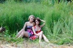 Zwei junge blonde Mädchen und braunhaarige Frau in den hellen Kleidern, die im Sommer aufwerfen, parken im hohen Gras Lizenzfreies Stockfoto