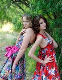 Zwei junge blonde Mädchen und eine braunhaarige Frau in den hellen Kleidern, die in einem Sommer aufwerfen, parken gegen einen Hi Lizenzfreie Stockfotos