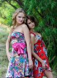 Zwei junge blonde Mädchen und eine braunhaarige Frau in den hellen Kleidern, die in einem Sommer aufwerfen, parken gegen einen Hi Stockfoto