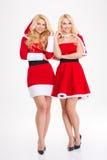 Zwei junge blonde Schwesterzwillinge in Weihnachtsmann-Kostümen Lizenzfreie Stockbilder