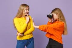 Zwei junge blonde Zwillingsschwestermädchen in der klaren bunten Kleidung, die Fotos auf der Retro- Weinlesefotokamera an lokalis stockbild