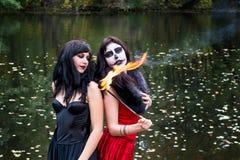 Zwei junge Brunettesfrauen mit Make-up mögen einen Halloween-Schädel und Lizenzfreie Stockfotografie