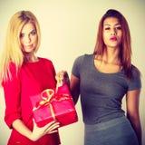 Zwei junge Damen mit rotem Geschenk stockfotos