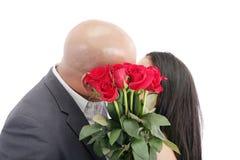 Zwei junge Daten, die hinter einem Blumenstrauß von roten Rosen küssen lizenzfreie stockfotos