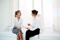 Zwei junge erfolgreiche weibliche Geschäftsführer, die digitale Tablette verwenden, während neue Geschäftsideen besprechen Sie, Stockbild