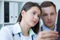Zwei junge ernste überzeugte Doktoren, die den Röntgenstrahl ihres Patienten überprüfen und eine Diagnose machen Radiologe oder stockfotos