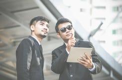 Zwei junge ernste Geschäftsmänner unter Verwendung einer digitalen Tablette und eines pointin Lizenzfreie Stockbilder