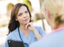 Zwei junge erwachsene Ärztinnen oder Nuses, die draußen sprechen Lizenzfreie Stockbilder