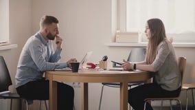 Zwei junge europäische Geschäftsleute haben ein ernstes Gespräch durch die Tabelle im modernen hellen Büro, weiblicher Chef aufko stock video