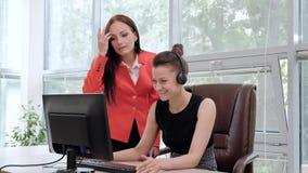 Zwei junge Frauen arbeiten in einem hellen Büro am Computer Besprechen Sie Arbeitsflüsse und genießen Sie ein erfolgreiches Abkom stock footage