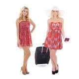 Zwei junge Frauen in den roten Kleidern mit dem Koffer bereit, Urlaub zu machen i Stockfotos