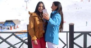 Zwei junge Frauen, die über ihr selfie lachen lizenzfreie stockbilder