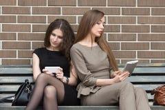 Zwei junge Frauen, die auf Bank unter Verwendung ihrer eigenen Geräte sitzen Lizenzfreie Stockbilder