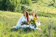 Zwei junge Frauen, die auf dem Gebiet sitzen lizenzfreies stockfoto
