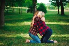 Zwei junge Frauen, die auf dem Grasumarmen sitzen stockfotos