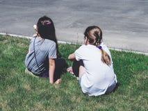 Zwei junge Frauen, die auf Gras, hintere Ansicht sitzen lizenzfreie stockbilder