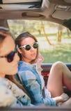 Zwei junge Frauen, die das Sitzen innerhalb des Autos stillstehen Stockfoto