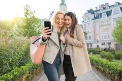 Zwei junge Frauen, die den Spaß, den lachenden Smartphone betrachtend, sonniger Herbsttag, Stadthintergrund, goldene Stunde haben lizenzfreie stockfotos
