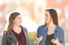 Zwei junge Frauen, die in der Straße gehen und sprechen stockfoto