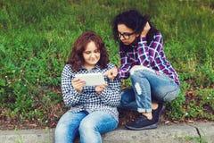 Zwei junge Frauen, die draußen Tablet-Computer verwenden Stockfotos