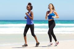 Zwei junge Frauen, die durch Wasser auf Strand laufen Lizenzfreie Stockfotografie