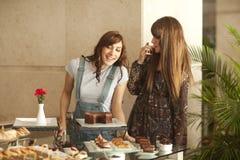 Zwei junge Frauen, die ein Nachtischbuffet genießen Stockfotografie