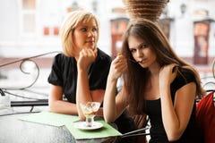 Zwei junge Frauen, die eine Eiscreme essen Lizenzfreie Stockfotos