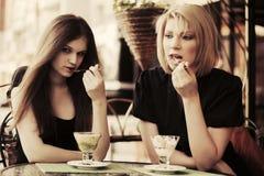 Zwei junge Frauen, die eine Eiscreme am Straßencafé essen Stockbild