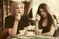 Zwei junge Frauen, die eine Eiscreme am Straßencafé essen Lizenzfreies Stockbild